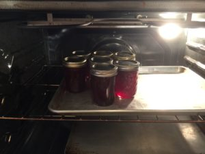 jars of strawberry jam warming in oven