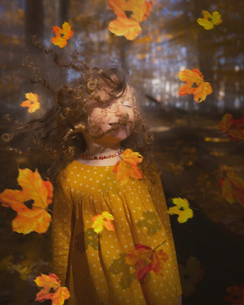 A girl closing her eyes as the leaves fall all around #heatherearles #herbnwisdom #naturalliving #fall #autum #seasons