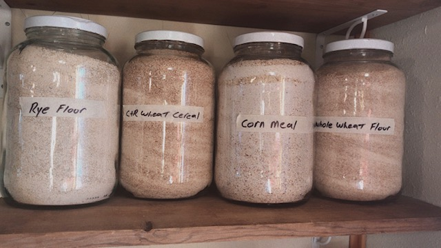 Gallon jars full of wheat flour and cornmeal #heatherearles #herbnwisdom #naturalliving #grindingwheat #heritagecorn